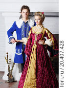 Young couple in colored medieval costumes stand next to fireplace., фото № 20407428, снято 2 ноября 2013 г. (c) Losevsky Pavel / Фотобанк Лори