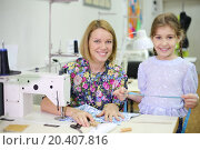 Купить «Female tailor sits at table with sewing machine with student girl and smiles. Focus on woman.», фото № 20407816, снято 27 апреля 2013 г. (c) Losevsky Pavel / Фотобанк Лори