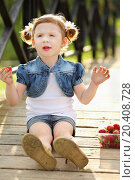 Little pretty girl sits on wooden bridge and eats strawberries at sunny day., фото № 20408728, снято 29 мая 2013 г. (c) Losevsky Pavel / Фотобанк Лори