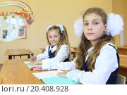Two girls in school uniform sit at wooden school desk with exercise books in classroom at school. Focus on right girl., фото № 20408928, снято 17 августа 2013 г. (c) Losevsky Pavel / Фотобанк Лори