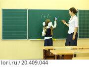 Купить «Girl and teacher near chalkboard solve simple math examples in classroom at school. Girl writes.», фото № 20409044, снято 17 августа 2013 г. (c) Losevsky Pavel / Фотобанк Лори
