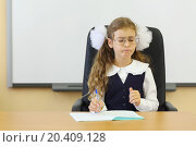Girl in glasses sits at teacher table with exercise book in classroom and thinks at school., фото № 20409128, снято 17 августа 2013 г. (c) Losevsky Pavel / Фотобанк Лори