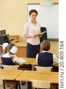Купить «Teacher with book looks at pupils sitting at desks in classroom at school.», фото № 20409164, снято 17 августа 2013 г. (c) Losevsky Pavel / Фотобанк Лори