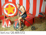 Athlete with grimace riding circus retro bike. Стоковое фото, фотограф Losevsky Pavel / Фотобанк Лори