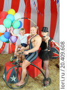 Three happy circus strong man, woman in cylinder and boy on retro bike with balloons in striped tent. Стоковое фото, фотограф Losevsky Pavel / Фотобанк Лори
