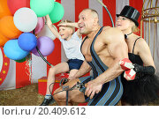 Funny circus family riding on retro bike with balloons in striped tent. Стоковое фото, фотограф Losevsky Pavel / Фотобанк Лори