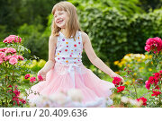 Купить «Laughing little girl dressed in suit with puffy skirt stand among rosebushes in summer park», фото № 20409636, снято 2 июля 2013 г. (c) Losevsky Pavel / Фотобанк Лори