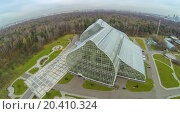 Купить «MOSCOW - OCT 23: View from unmanned quadrocopter to futuristic glass building of Main Greenhouse Botanical Garden against trees and lawns on October 23, 2013 in Moscow, Russia.», фото № 20410324, снято 23 октября 2013 г. (c) Losevsky Pavel / Фотобанк Лори
