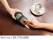 Купить «close up of hands with credit card reader at cafe», фото № 20716688, снято 1 декабря 2015 г. (c) Syda Productions / Фотобанк Лори