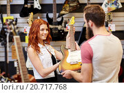 Купить «assistant showing customer guitar at music store», фото № 20717768, снято 11 декабря 2014 г. (c) Syda Productions / Фотобанк Лори