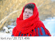 Купить «Elderly woman in red knitted scarf on her head outdoors», фото № 20721496, снято 5 января 2016 г. (c) Володина Ольга / Фотобанк Лори