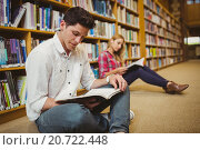 Купить «Concentrated students working on floor», фото № 20722448, снято 6 июля 2015 г. (c) Wavebreak Media / Фотобанк Лори
