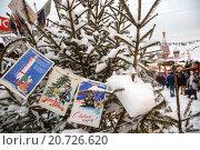 Купить «Новогодние советские открытки с поздравлением с Новым годом весят на елке на рождественской ярмарке на Красной площади города Москвы, Россия», фото № 20726620, снято 17 января 2016 г. (c) Николай Винокуров / Фотобанк Лори
