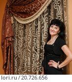 Купить «Счастливая тёмноволосая женщина средних лет стоит возле красивой шторы», эксклюзивное фото № 20726656, снято 12 июля 2015 г. (c) Игорь Низов / Фотобанк Лори