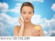 Купить «young woman applying cream to her face», фото № 20732240, снято 31 октября 2015 г. (c) Syda Productions / Фотобанк Лори