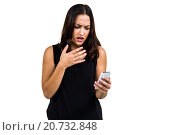 Купить «Shocked woman using phone», фото № 20732848, снято 28 мая 2015 г. (c) Wavebreak Media / Фотобанк Лори
