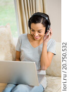 Купить «Smiling brunette using laptop and headphones», фото № 20750532, снято 15 июля 2015 г. (c) Wavebreak Media / Фотобанк Лори