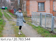 Купить «Женщина в сером пальто машет рукой», эксклюзивное фото № 20783544, снято 19 ноября 2011 г. (c) Юрий Морозов / Фотобанк Лори