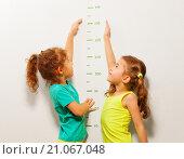 Купить «Две маленькие очаровательные девочки измеряют свой рост около стены с отметками», фото № 21067048, снято 12 декабря 2015 г. (c) Сергей Новиков / Фотобанк Лори