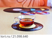 Старые виниловые пластинки и CD-диски на деревянном столе. Чашка чая стоит на пластинке, фон размыт. Стоковое фото, фотограф Александр Замоткин / Фотобанк Лори