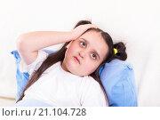 Купить «Девочка заболела и лежит держа голову рукой», фото № 21104728, снято 25 января 2016 г. (c) Emelinna / Фотобанк Лори