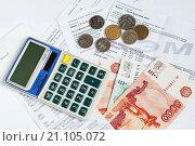 Купить «Российские деньги и калькулятор лежат на квитанциях для оплаты коммунальных услуг», эксклюзивное фото № 21105072, снято 25 января 2016 г. (c) Игорь Низов / Фотобанк Лори