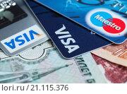 Пластиковые карты лежат на российских деньгах крупным планом (2016 год). Редакционное фото, фотограф Игорь Низов / Фотобанк Лори
