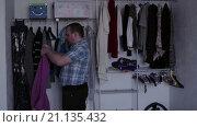Купить «Мужчина надевает свитер», видеоролик № 21135432, снято 22 января 2016 г. (c) Валентин Беспалов / Фотобанк Лори