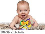Улыбающийся ребенок на кровати с игрушками. Стоковое фото, фотограф Ирина Столярова / Фотобанк Лори