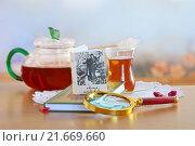 Миниатюрная книга с лупой и чашкой чая на деревянном столе. Стоковое фото, фотограф Татьяна Белова / Фотобанк Лори