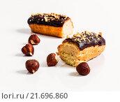 Шоколадные эклеры с фундуком на белом столе. Стоковое фото, фотограф Riasna Yuliia / Фотобанк Лори