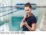 Pretty trainer looking at stopwatch with whistle. Стоковое фото, агентство Wavebreak Media / Фотобанк Лори