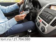 Купить «close up of man with smartphone driving car», фото № 21704080, снято 17 июля 2015 г. (c) Syda Productions / Фотобанк Лори