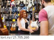 Купить «assistant showing customer guitar at music store», фото № 21705260, снято 11 декабря 2014 г. (c) Syda Productions / Фотобанк Лори