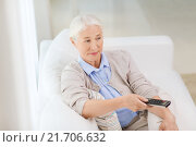 Купить «senior woman with remote watching tv at home», фото № 21706632, снято 10 июля 2015 г. (c) Syda Productions / Фотобанк Лори