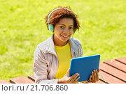 Купить «happy african woman with tablet pc and headphones», фото № 21706860, снято 4 июня 2015 г. (c) Syda Productions / Фотобанк Лори