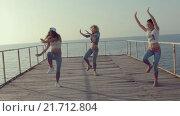 Три энергичные девушки танцуют тверк на деревянном причале вблизи моря (2015 год). Редакционное видео, видеограф Denis Mishchenko / Фотобанк Лори