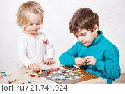 Купить «Дети собирают мозаику на столе», фото № 21741924, снято 23 декабря 2015 г. (c) Ирина Мойсеева / Фотобанк Лори