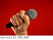 Купить «Микрофон в мужской руке на красном фоне», фото № 21765244, снято 4 февраля 2016 г. (c) Anton Eine / Фотобанк Лори