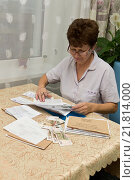 Купить «Пожилая женщина проверяет счета за коммунальные услуги», фото № 21814000, снято 30 сентября 2015 г. (c) Лариса Капусткина / Фотобанк Лори
