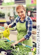 Купить «happy woman with watering can in greenhouse», фото № 21814216, снято 25 февраля 2015 г. (c) Syda Productions / Фотобанк Лори