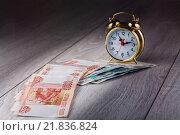 Купить «Деньги - экономят время. Купюры и часы», эксклюзивное фото № 21836824, снято 16 февраля 2016 г. (c) Юрий Шурчков / Фотобанк Лори