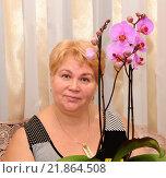 Женщина средних лет цветком орхидеи. Стоковое фото, фотограф Юрий Морозов / Фотобанк Лори