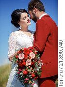 Купить «Невеста в белом платье и жених в красном костюме стоят на фоне синего неба», фото № 21890740, снято 30 августа 2015 г. (c) Евгений Майнагашев / Фотобанк Лори