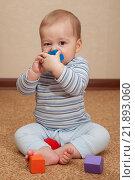 Ребенок сидит на полу и грызет игрушку. Стоковое фото, фотограф Ирина Столярова / Фотобанк Лори