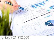 Купить «Мужская рука с ручкой на документах с графиками», фото № 21912500, снято 7 февраля 2016 г. (c) Елена Саклакова / Фотобанк Лори