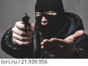 Купить «Грабитель в маске целится из пистолета», фото № 21939956, снято 19 февраля 2016 г. (c) Mark Agnor / Фотобанк Лори