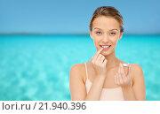 Купить «smiling young woman applying lip balm to her lips», фото № 21940396, снято 31 октября 2015 г. (c) Syda Productions / Фотобанк Лори