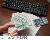 Купить «Зарплата. Девушка держит в руках российские рубли на фоне трудового договора», эксклюзивное фото № 21942996, снято 25 февраля 2016 г. (c) Игорь Низов / Фотобанк Лори