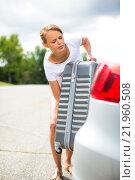 Купить «Young woman putting a have suitcase into her car's trunk», фото № 21960508, снято 16 июля 2019 г. (c) PantherMedia / Фотобанк Лори